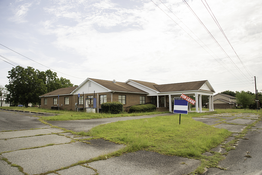 A rundown residential and commercial property in a suburban area with a for lease sign. leasing mistakes to avoid